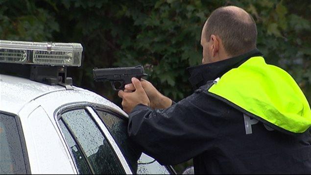 Un policier pointe son arme ver la demeure où le suspect demeurait terré.