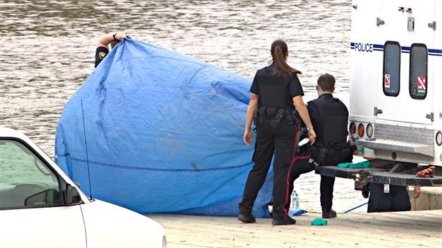 Les policiers ont recouvert d'une toile le corps d'une femme repêché dans la rivière Rouge, près du quai Alexander, le 17 août.
