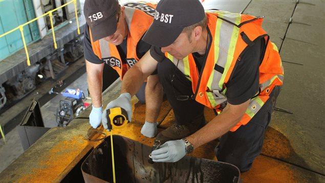 Des enquêteurs du Bureau de la sécurité dans les transports du Canada évaluent la cheminée de la locomotive de tête.