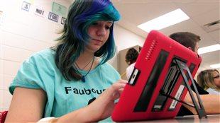 Une adolescente utilise un iPad fourni par son école.