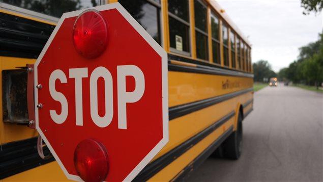 Un autobus scolaire fait son premier arrêt au Collège Louis-Riel lors de la rentrée scolaire 2014.