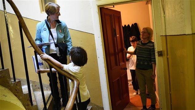 Une famille discute avec une volontaire qui fait campagne pour le Oui en Écosse.