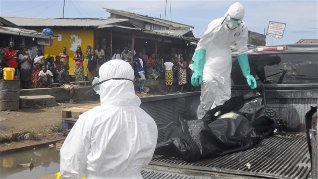 Des travailleurs de la santé transportent le corps d'une victime présumée du virus Ebola, près de Monrovia, au Liberia, le 1er octobre 2014.
