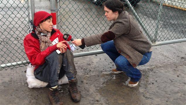 Une des manifestantes attachées à une des portes menant à la raffinerie de Suncor à Montréal-Est