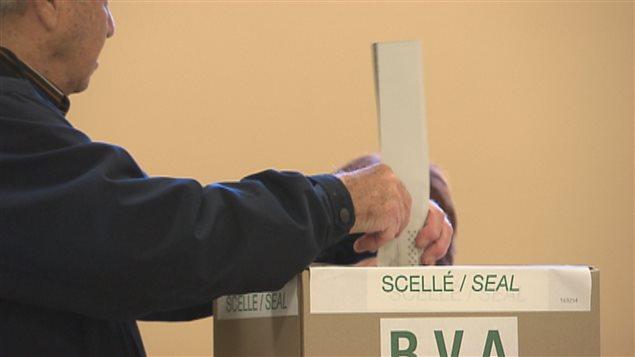 Un électeur dépose son bulletin de vote dans une urne.