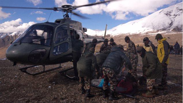 Des secouristes népalais s'apprêtent à hisser un radonneur dans un hélicoptère.