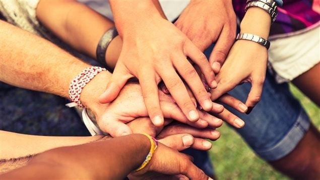 Un groupe de personnes joignent leurs mains