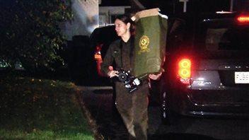 Une policière quitte la maison du suspect abattu avec un sac de documents.
