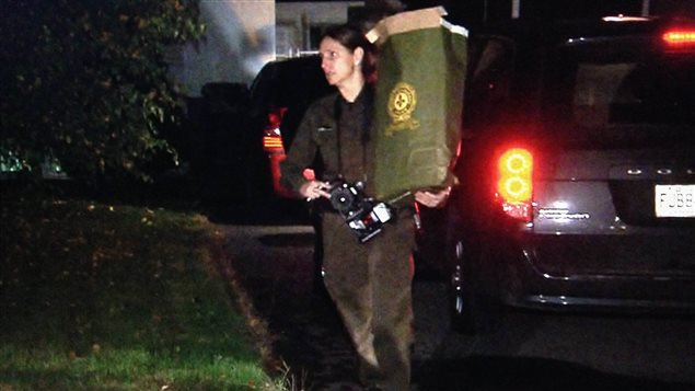 Une policière de la SQ tient un sac de preuves saisies au domicile du père de Martin Rouleau.