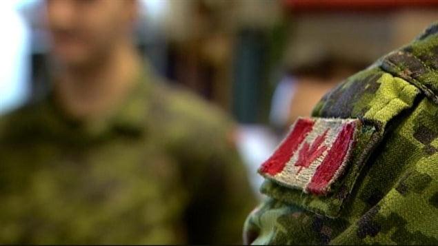 Un soldat porte l'uniforme avec le drapeau canadien sur l'épaulette