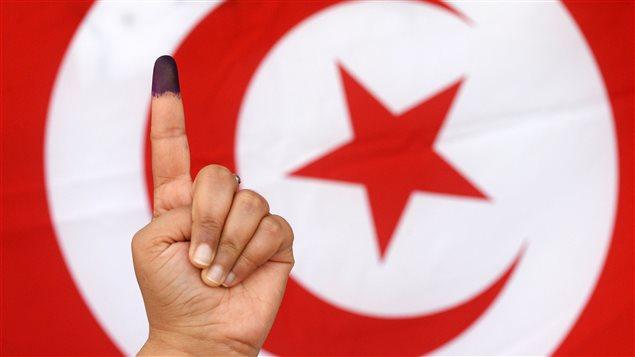 Une Tunisienne montre son doigt taché d'encre devant un drapeau du pays, après avoir voté.