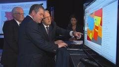 Le responsable de la Chaire VISAJ, Michel Perron, montre la plateforme CartoJeunes au ministre Yves Bolduc.