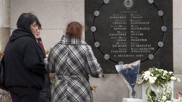 Des femmes se recueillent devant une plaque commémorative rappelant la tuerie de Polytechnique.