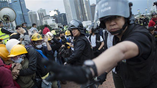 Des policiers tentaient de dégager la route Lung Wo, lundi.