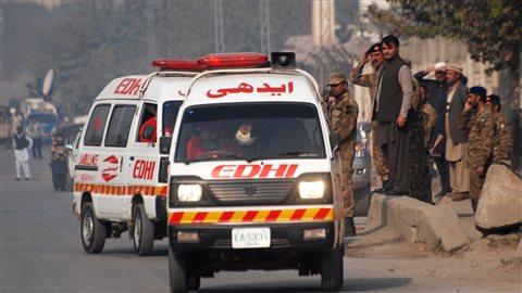 Des ambulances s'éloignent de l'école qui a été attaquée et dont l'assaut a fait un certain nombre de victimes.