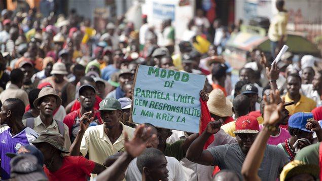Des manifestants réclament la démission du président Martelly à Port-au-Prince, le 5 décembre 2014. On peut lire sur l'affiche « Pamela White [l'ambassadrice américaine] a une responsabilité dans la crise ».