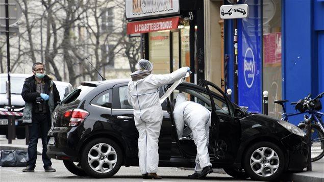 Des policiers passent au peigne fin la voiture utilisée par les auteurs de la fusillade, qui a été retrouvée rue de Meaux, dans le 19e arrondissement.