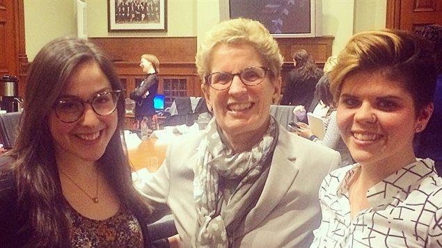 La première ministre Kathleen Wynne en compagnie de deux étudiantes de la Fédération canadienne des étudiants, dont Anna Goldfinch