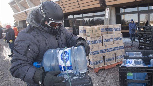 Un homme pose une bouteille d'eau sur sa bicyclette à Longueuil.