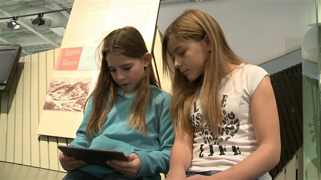 Deux élèves consultent l'application mobile du Musée de la Gaspésie.