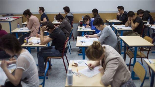 Des étudiants passent un examen dans une salle de classe.