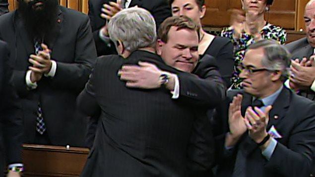 John Baird reçoit l'accolade du premier ministre Harper après l'annonce de son départ de la vie publique.