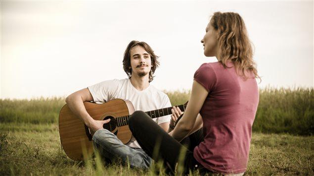 Un guitariste et une chanteuse sont assis dans un champs.