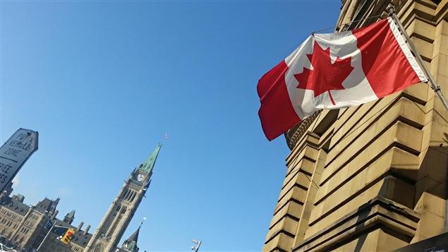 Le drapeau canadien flotte sur un édifice devant la colline du Parlement, à Ottawa, le 6 février 2015.