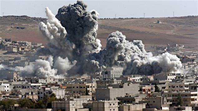 Cette photo datant du 22 octobre 2014 montre les résultats d'une attaque aérienne contre l'EI menée sur Kobani, en Syrie, par la coalition dirigée  par les États-Unis.