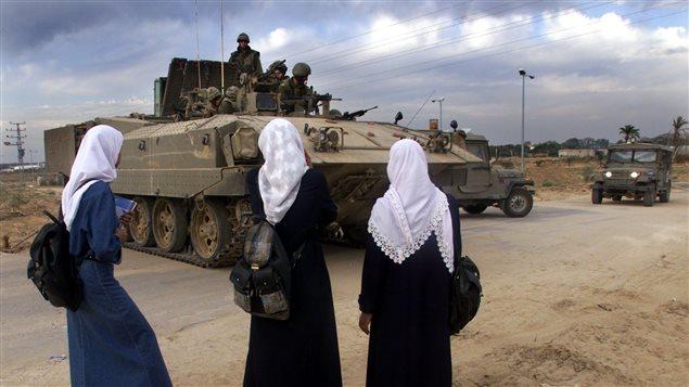 Des étudiantes palestiniennes face à un char israélien, à Gaza
