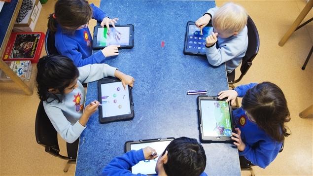 Des enfants apprennent en jouant sur une tablette.