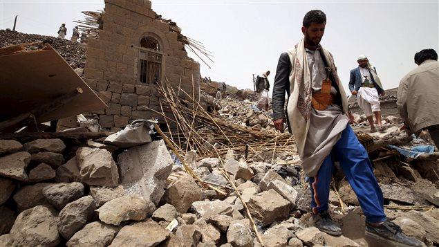 Des résidents sur les décombres de maisons détruites par une frappe aérienne dans un village près de Sanaa.