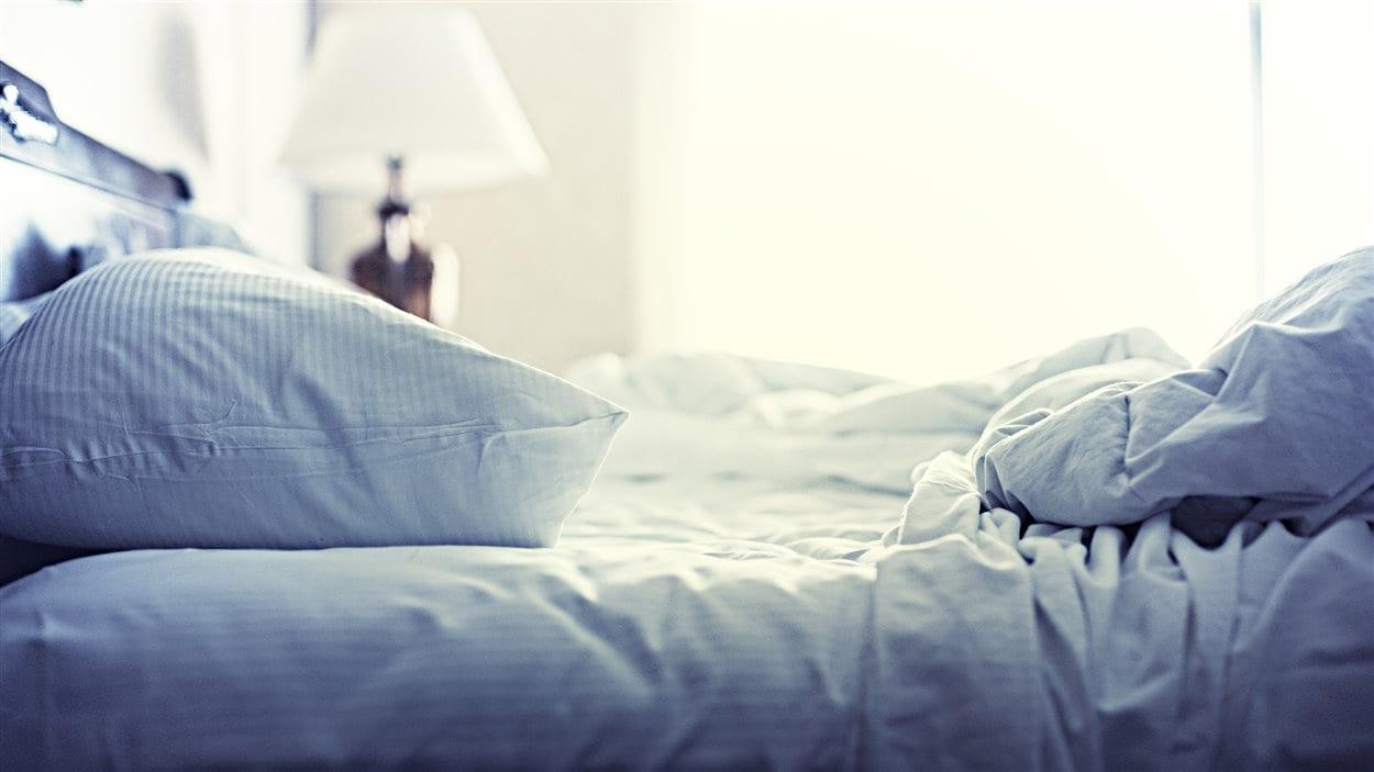 Un lit défait avec un oreiller.