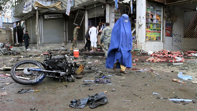 Une Afghane marche sur les lieux d'une attaque suicide à Jalalabad, qui a tué 33 personnes.