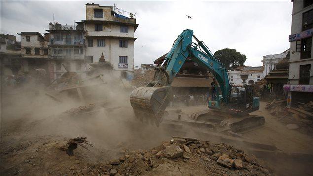 Une excavatrice creuse les décombres à la recherche de corps, à Katmandou.