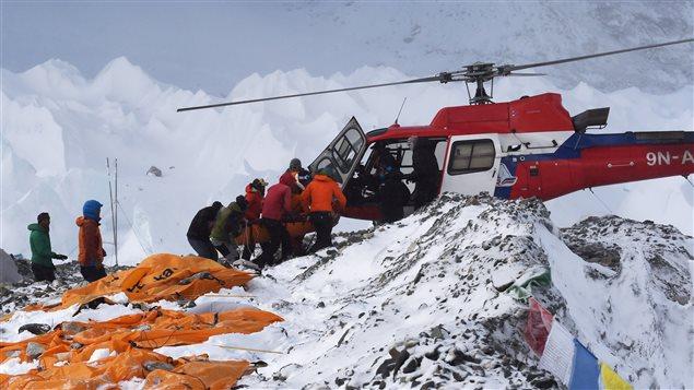 Des secouristes transportent une personne blessée à bord d'un hélicoptère au camp de base du mont Everest.