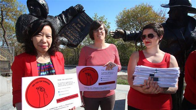 Trois femmes soutenant la campagne de Canadian Menstruators devant la statue de Célèbres cinq, sur la colline Parlementaire.