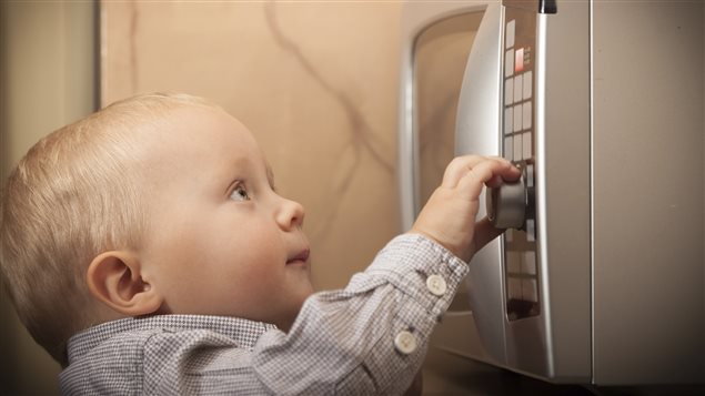 Un bébé devant un four micro-ondes