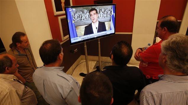 Des Grecs regardent l'allocution télévisée du premier ministre Alexis Tsipras après la victoire du non.
