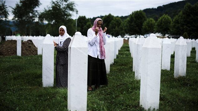 Des Bosniaques prient à côté de la tombe de leurs proches au mémorial de Potocari, près de Srebrenica, le 9 juillet 2015.
