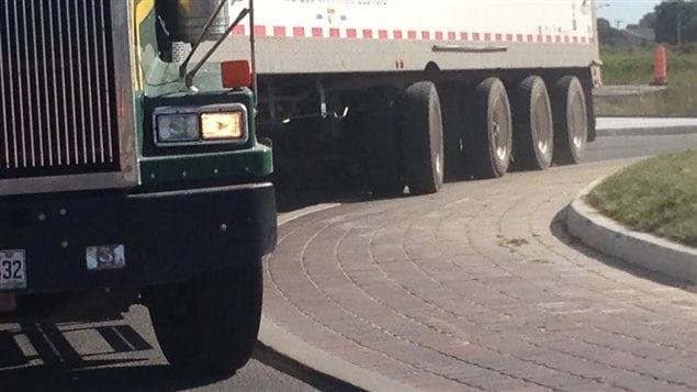 Camion qui roule sur le trottoir en empruntant le carrefoir giratoire du District 55