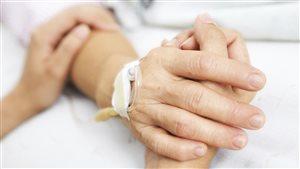 Une femme tient la main de sa mère à l'hôpital.