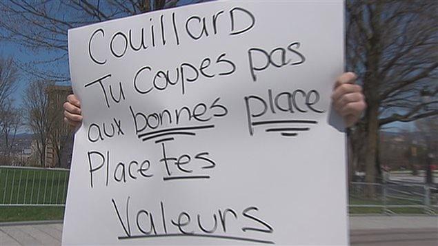 « Couillard, tu coupes pas aux bonnes places. Place tes valeurs », peut-on lire sur l'affiche d'un militant. (archives)