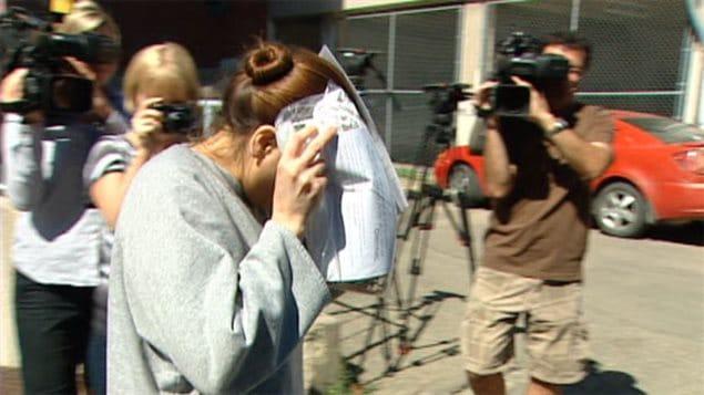 Tammy Goforth, accusée de meurtre non prémédité contre une fillette de 4 ans, se couvre le visage à la sortie du palais de justice de Regina en 2013.