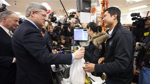Le premier ministre Stephen Harper achète du sirop d'érable au dépanneur de David Chen, à Toronto, avant son annonce sur la présentation de la Loi sur l'arrestation par un citoyen et sur la légitime défense, le 17 février 2011.