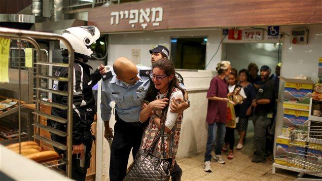 Un soldat israélien console une jeune femme à la sortie d'un supermarché où est survenue une attaque au couteau