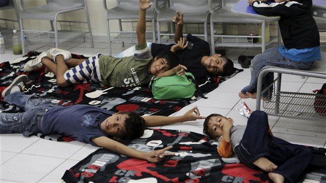 Des enfants sont couchés par terre en attendant les prochains vols, à l'aéroport de Puerto Vallarta