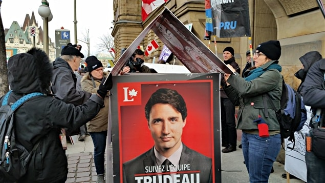 Des manifestants en train de construire une maison avec des pancartes électorales de Justin Trudeau.