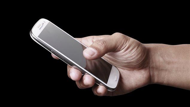 Un homme tient un téléphone intelligent.