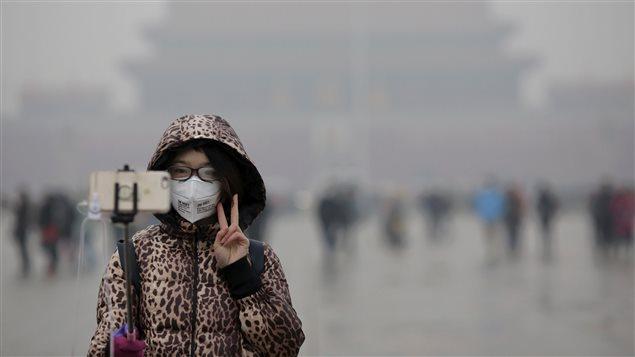 Un jeune femme se prend en photo lors d'une cérémonie à la place Tiananmen, à Pékin.